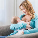 Beautiful mom breastfeeds her daughter at home. They are sitting on the sofa.